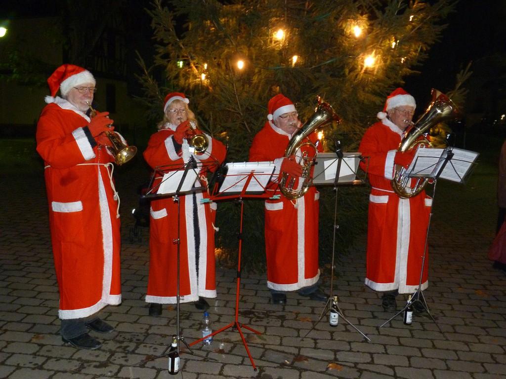 Der Weihnachtsbaum wird aufgestellt, Mitglieder des Blasochesters Höchst untermalen das kleine Fest mit weihnachtlicher Musik.
