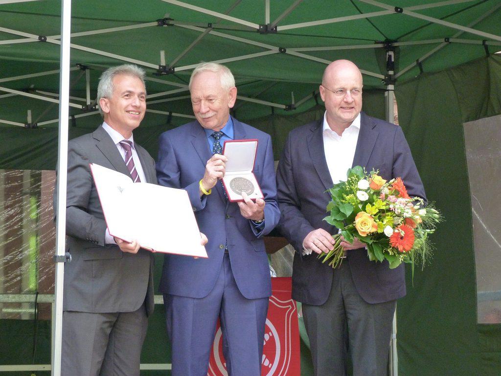 Oberbürgermeister Peter Feldmann, Ernst-Josef Robiné mit Ehrenplakette und Gratulant Jürgen Vormann